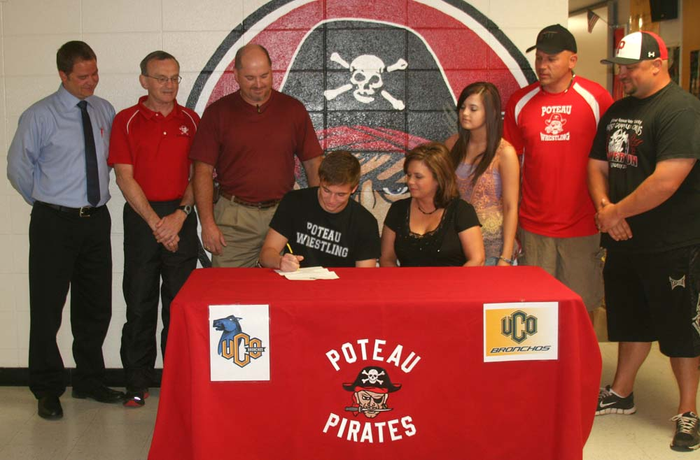Photo by DAVID SEELEY of Poteau Daily News. Poteau senior Tyler Tustin signs to wrestle with UCO. Seated next to him is his mother, Cindy. Back row: Cory Wood, coach Jack Hornbuckle, his father Bret, sister Tarah, and assistant coaches Dewayne Hornbuckle and Chris Ford.