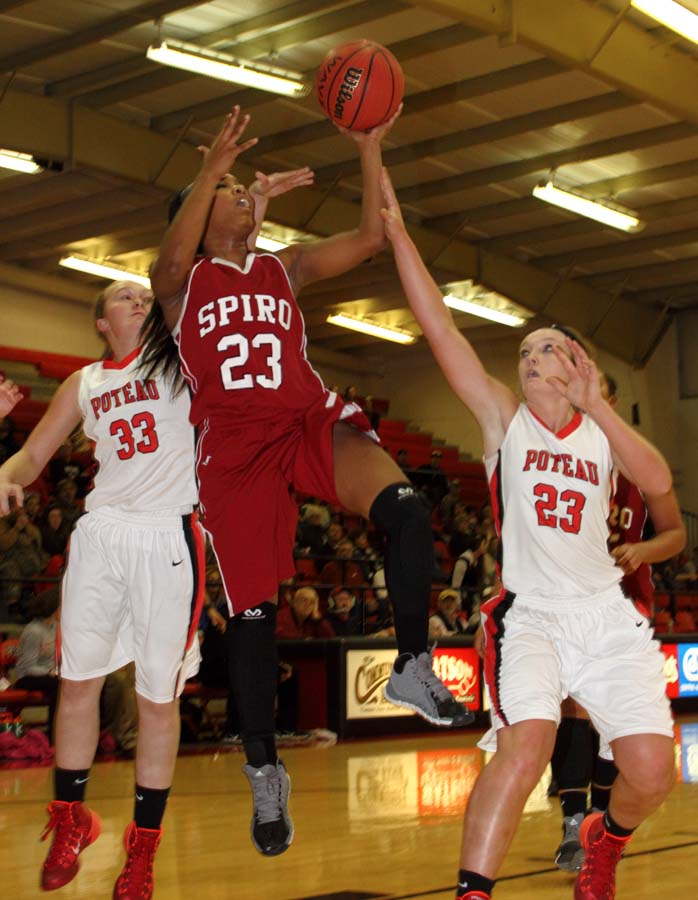 Spiro's Kanisha Hutchinson drives between Poteau's Chelsey Campbell and Kaitlan Standridge for a basket