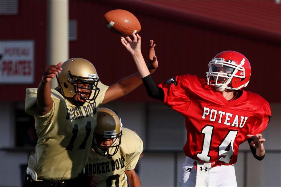 Poteau's Jett Pitchford gets a pass away as two Broken Bow defenders pressure him