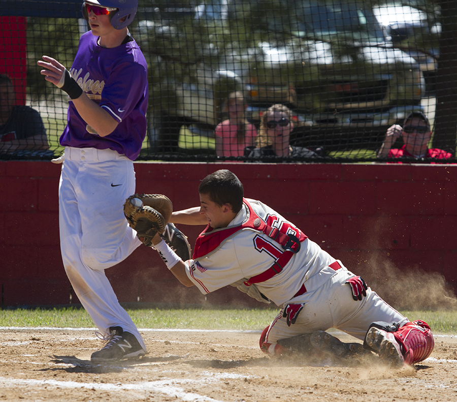 Howe catcher Carson McGee tags out Heavener's Dillion May at home plate