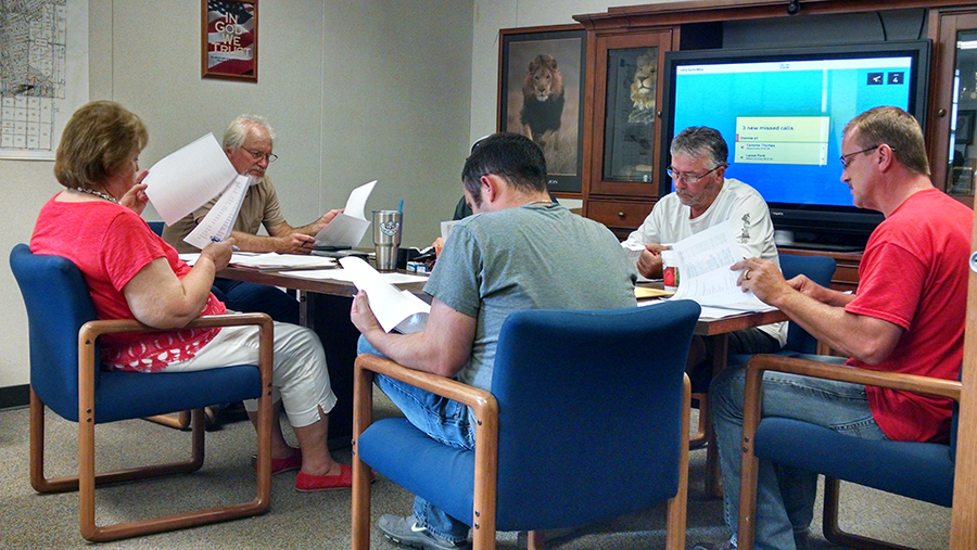 Howe superintendent Scott Parks, right, and the school board look over the agenda for Monday's meeting