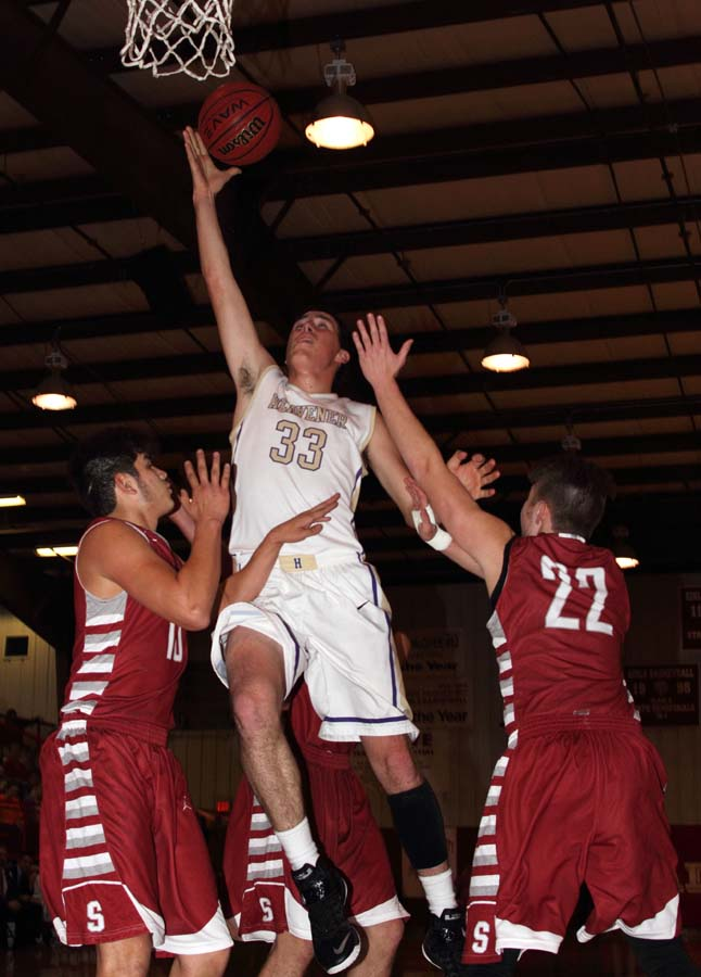 Heavener's Colt Dunigan goes up for a shot between Spiro defenders