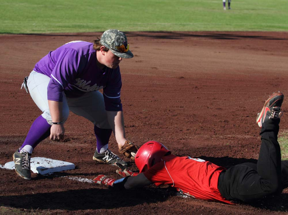 Heavener's Grant Shipman tags out Roger Barcheers in the first inning