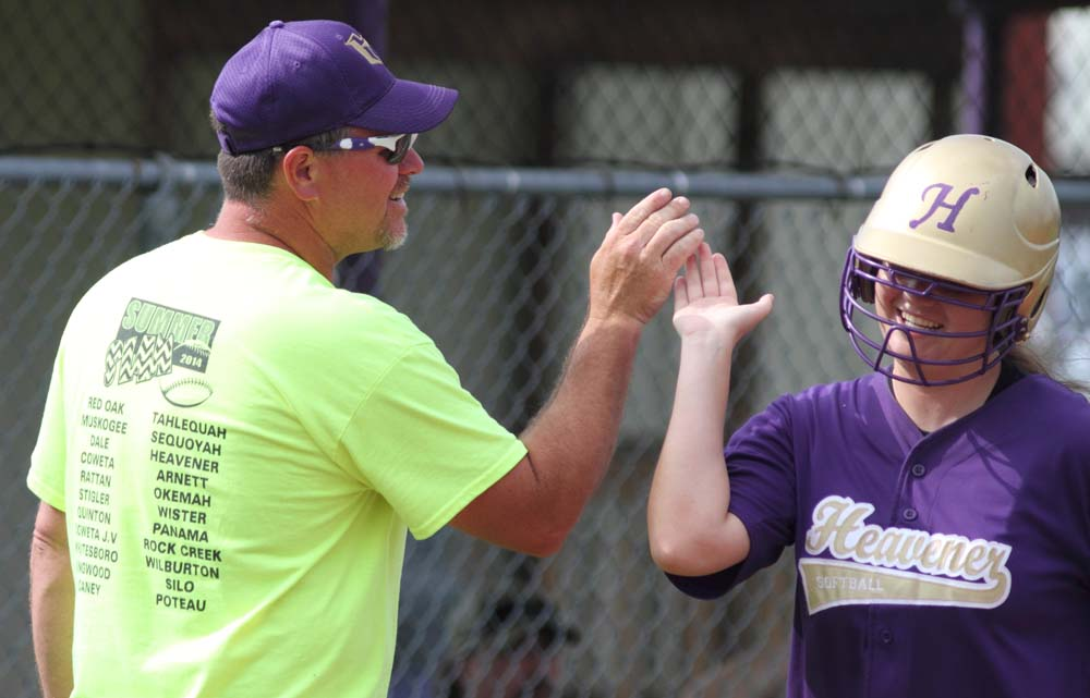 Heavener's Lakota Vickers is congratulated by coach Rodale Sanders after hitting a three-run home run against Talihina.