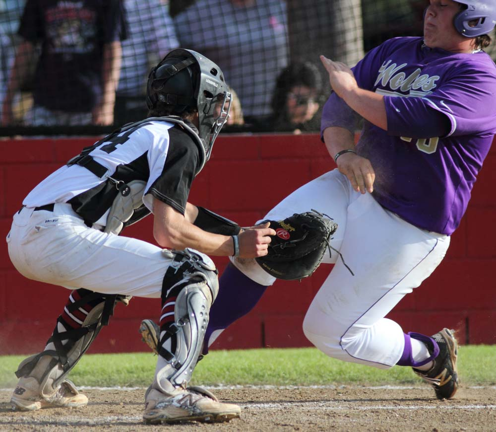 Heavener's Grant Shipman is tagged out at home by Spiro's Alex Demato in the Bulldogs' 6-2 win