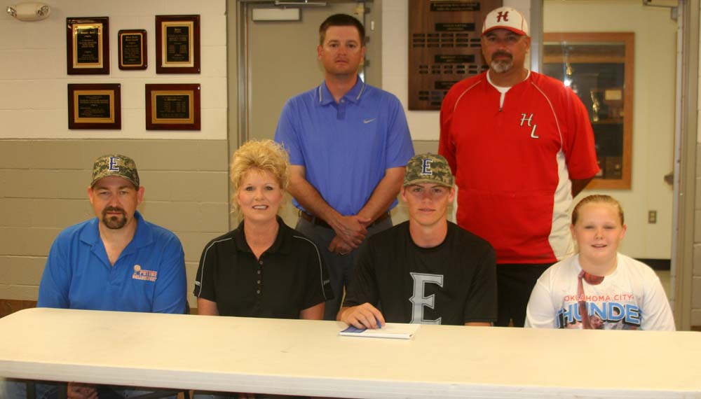 Photo by DAVID SEELEY/PDN. Howe baseball player Chase Blake, front row, second from right, signs a letter of intent with Eastern Oklahoma State College in a signing ceremony Friday morning inside the Howe Gym. Sharing the moment are, front row, from left, father, Jason, mother, Sandy and sister, Jayce along with, back row, from left, EOSC coach Craig Price and Howe coach Jon Sockey.