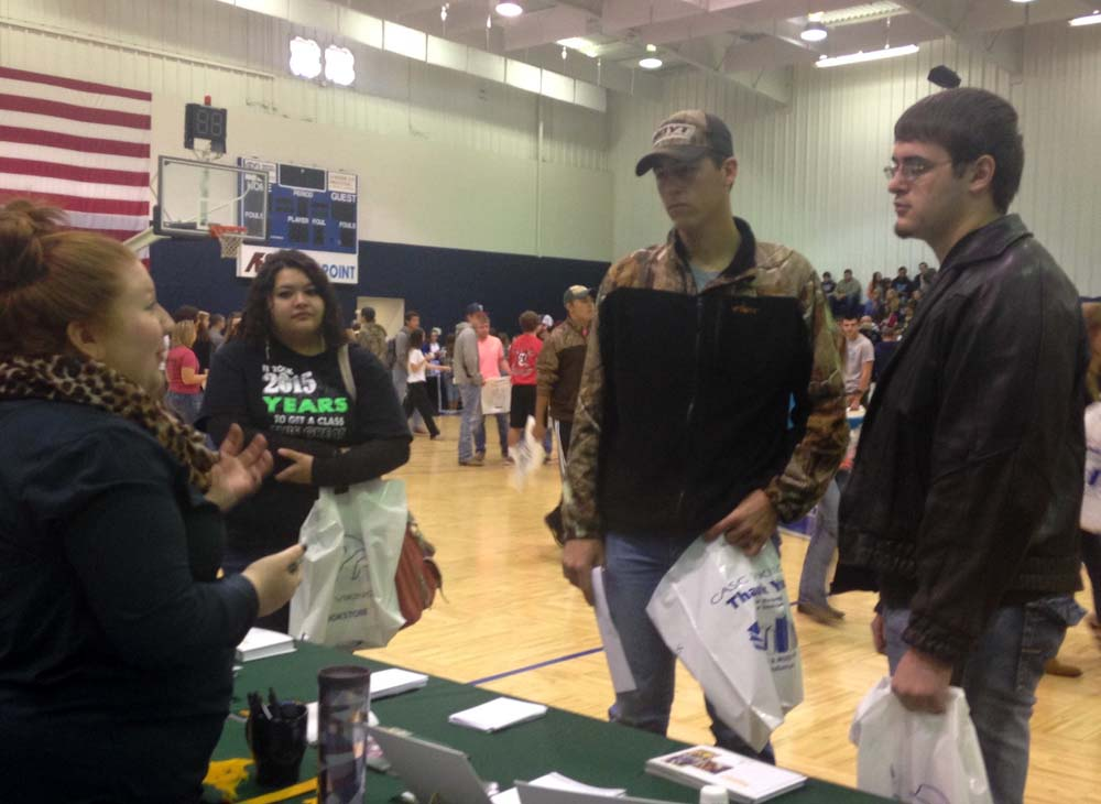 Photo by JANET HURST. Heavener seniors Audri Garcia, Colt Dunigan and Dalton Clark talk with a representative at the college fair