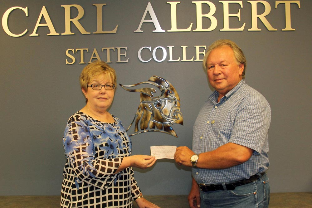 Kathy Quirk, left, accepts a check from Ronnie Smith