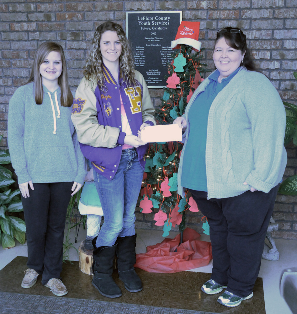 Pictured are Heavener National Honor Society Vice-President Andrea Nicholson and President Shaylie Sanders making a donation to Leflore County Youth Services representative Terri Krebs.